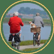 Two men biking by waterside