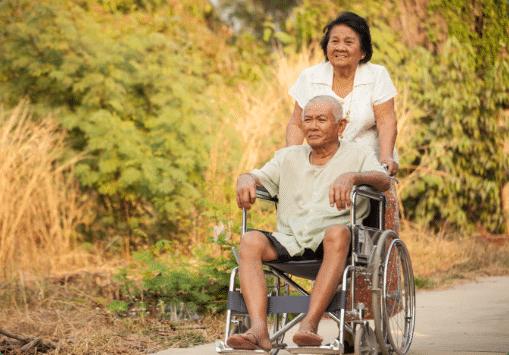 A woman pushing a man in a wheelchair